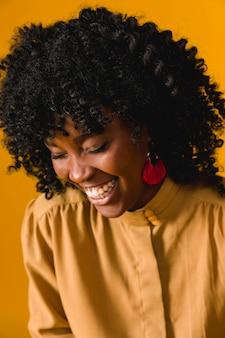 Młoda kobieta afroamerykanów śmieje się z zamkniętymi oczami