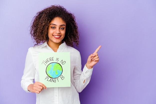 Młoda kobieta afroamerykanów trzyma a nie ma planety b na białym tle, uśmiechając się i wskazując na bok, pokazując coś w pustej przestrzeni.