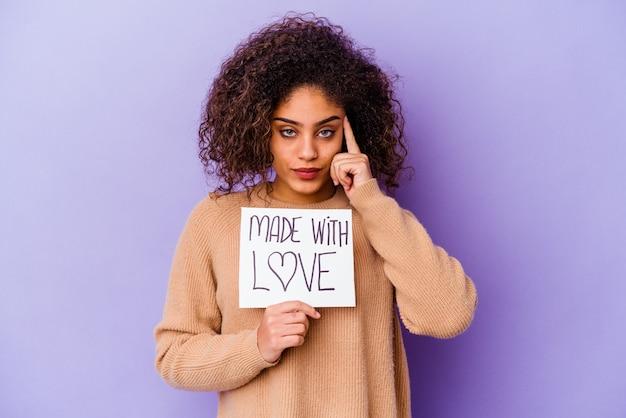 Młoda kobieta afroamerykanów trzyma afisz made with love na białym tle na fioletowej ścianie wskazując świątyni palcem, myśląc, koncentruje się na zadaniu.
