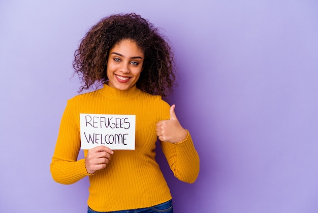 Młoda kobieta afroamerykanów trzyma afisz witamy uchodźców uśmiechnięty i podnoszący kciuk do góry