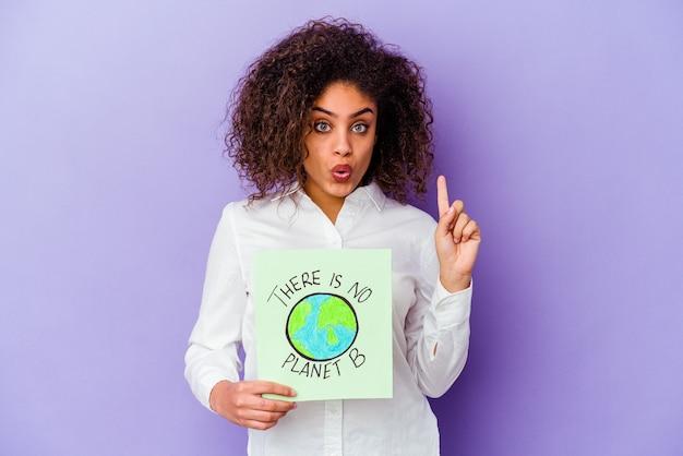 Młoda kobieta afroamerykanów trzyma planety b nie ma odizolowanej planety, mając jakiś świetny pomysł, pojęcie kreatywności.