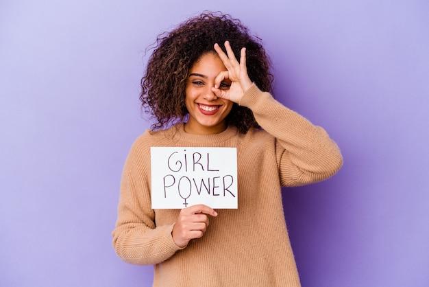 Młoda kobieta afroamerykanów trzyma tabliczkę moc girl na fioletowym podekscytowany utrzymując ok gest na oko.