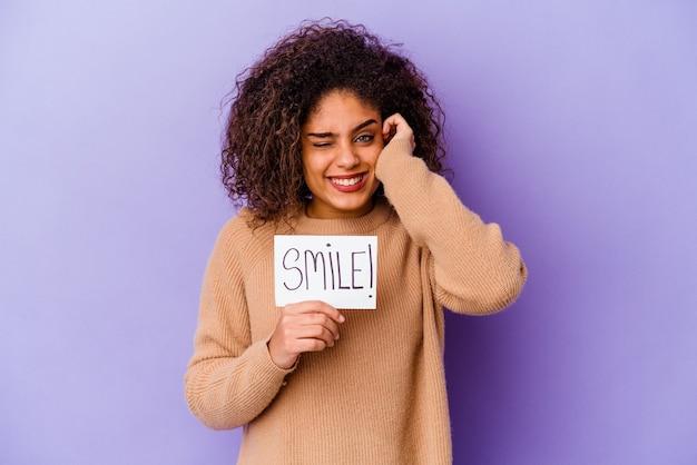 Młoda kobieta afroamerykanów trzyma tabliczkę smile na białym tle na fioletowe ściany obejmujące uszy rękami.