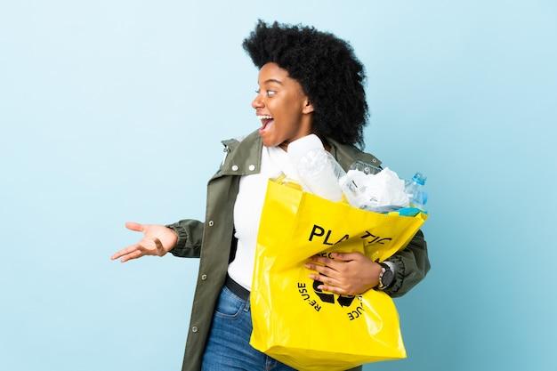 Młoda kobieta afroamerykanów trzyma torbę kosza z wyrazem zaskoczenia, patrząc z boku