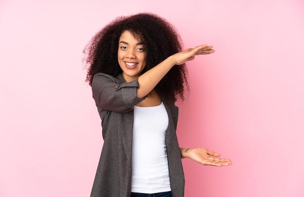 Młoda kobieta afroamerykanów trzymając copyspace do wstawienia reklamy