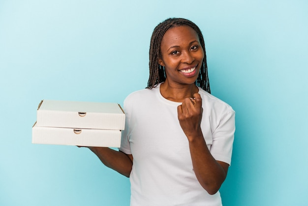 Młoda kobieta afroamerykanów trzymająca pizze na białym tle na niebieskim tle, wskazując palcem na ciebie, jakby zapraszając się bliżej.