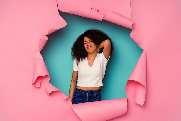 Młoda kobieta afroamerykanów w podarty papier na białym tle na niebieskim tle cierpi na ból szyi z powodu siedzącego trybu życia.