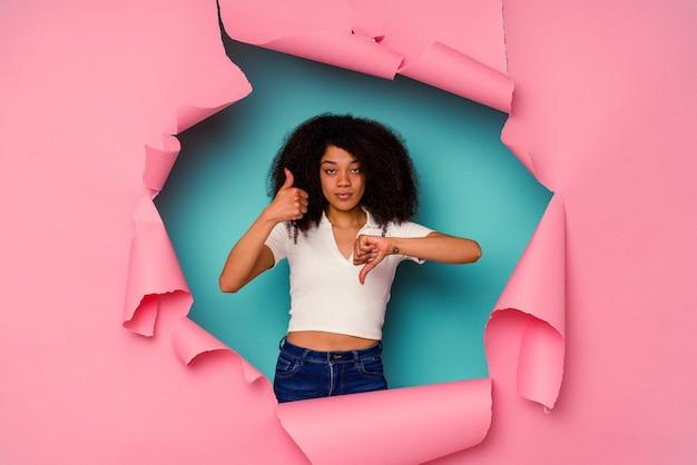 Młoda kobieta afroamerykanów w podarty papier na białym tle na niebieskim tle pokazuje kciuk w górę i w dół, trudno wybrać koncepcję