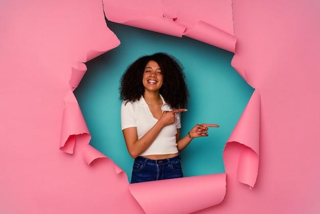Młoda kobieta afroamerykanów w rozdarty papier na białym tle na niebieskiej ścianie podekscytowany, wskazując palcami wskazującymi z dala.