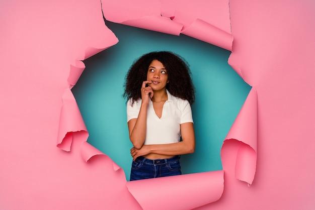 Młoda kobieta afroamerykanów w rozdarty papier na białym tle na niebieskim tle patrząc w bok z wyrazem wątpliwości i sceptycyzmu.