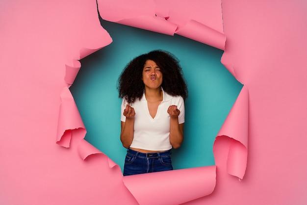 Młoda kobieta afroamerykanów w rozdarty papier na białym tle na niebieskim tle, pokazując, że nie ma pieniędzy.