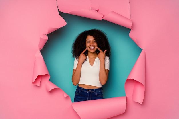 Młoda kobieta afroamerykanów w rozdarty papier na białym tle na niebieskim tle uśmiecha się, wskazując palcami na usta.