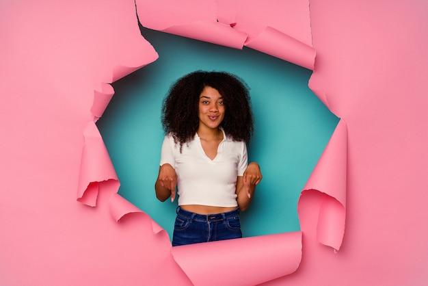 Młoda kobieta afroamerykanów w rozdarty papier na białym tle na niebieskim tle wskazuje w dół palcami, pozytywne uczucie.