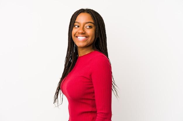 Młoda kobieta afroamerykanów wygląda na uśmiechnięty, wesoły i przyjemny.