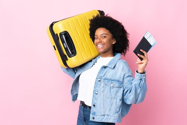 Młoda kobieta afroamerykanów wyizolowanych na różowo w wakacje z walizką i paszportem