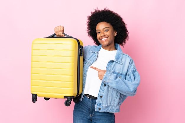 Młoda kobieta afroamerykanów wyizolowanych na różowo w wakacje z walizką podróżną