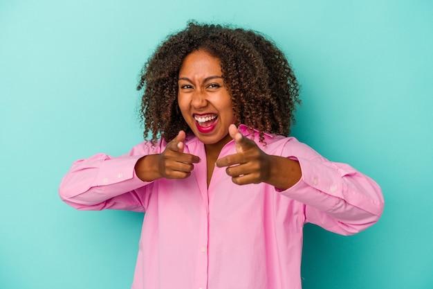 Młoda kobieta afroamerykanów z kręconymi włosami na białym tle na niebieskim tle wesołe uśmiechy skierowane do przodu.