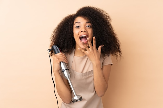 Młoda kobieta afroamerykanów za pomocą ręcznego blendera na białym tle na beż z wyrazem twarzy zaskoczenia