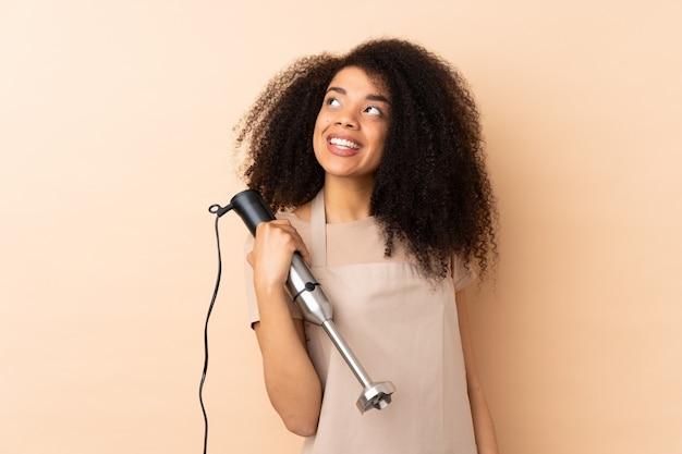 Młoda kobieta afroamerykanów za pomocą ręcznego blendera na białym tle na beżowym śmiechu i patrząc w górę