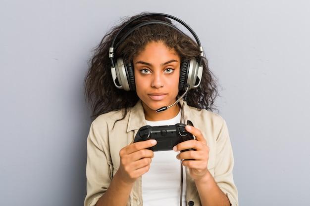 Młoda kobieta afroamerykanów za pomocą słuchawek i kontrolera gier