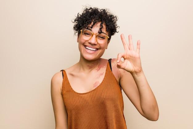 Młoda kobieta afroamerykanów ze znakiem urodzenia skóry mruga okiem i trzyma w porządku gest ręką.