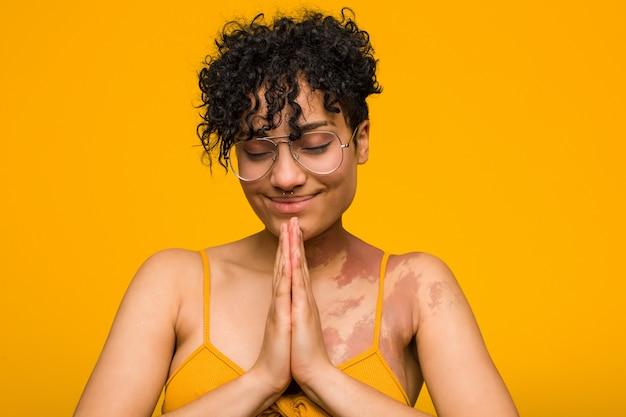 Młoda kobieta afroamerykanów ze znakiem urodzenia skóry, trzymając się za ręce w modlić się w pobliżu usta, czuje się pewnie.