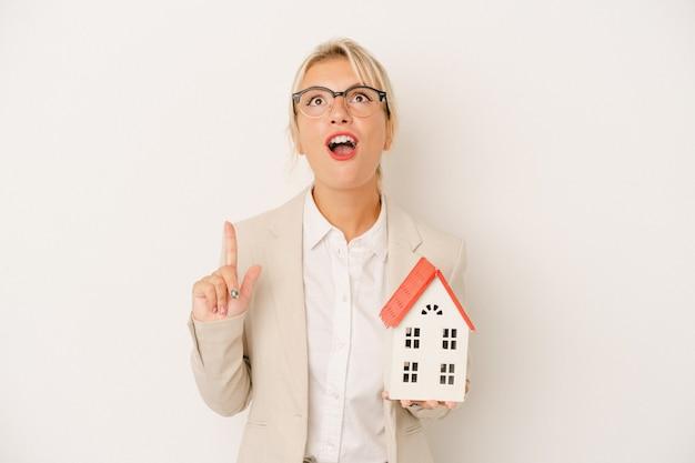 Młoda kobieta agenta nieruchomości trzyma model domu na białym tle, wskazując do góry z otwartymi ustami.