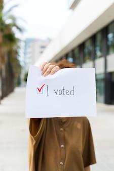 Młoda kobieta, aktywistka wzywa do głosowania, trzymając w ręku papier z oświadczeniem głosowałem. aktywizm polityczny, proces wyborczy, koncepcja pozycji aktywnego życia. prezydent, wybory do konstytucji.
