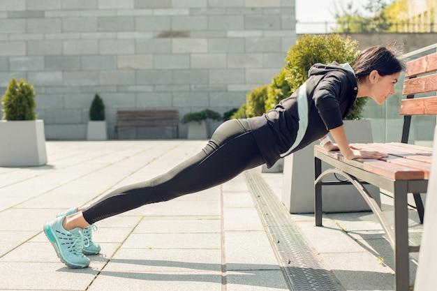Młoda kobieta aktywny trening ćwiczeń na ulicy poza pompkami
