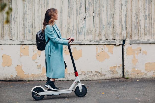 Młoda kobieta alternatywne dojazdy do pracy skuterem elektrycznym w niebieskim płaszczu w mieście