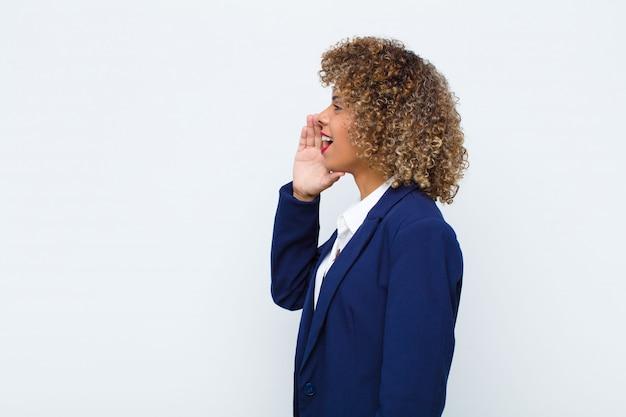 Młoda kobieta amerykanina afrykańskiego pochodzenia profilu widok, patrzejący szczęśliwy i podekscytowany, krzyczący i dzwoniący kopiować przestrzeń na stronie przeciw płaskiej ścianie