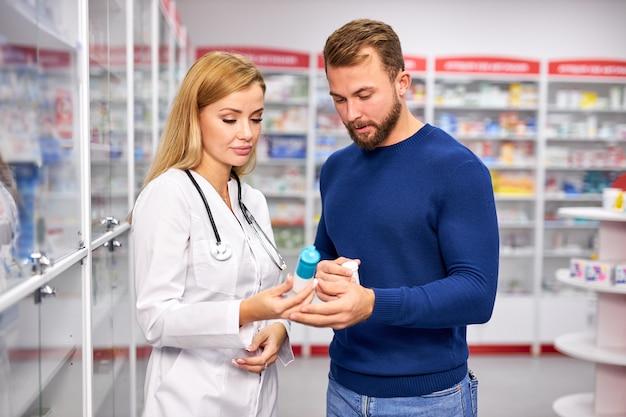 Młoda kobieta aptekarz z lekiem i męskim klientem w aptece