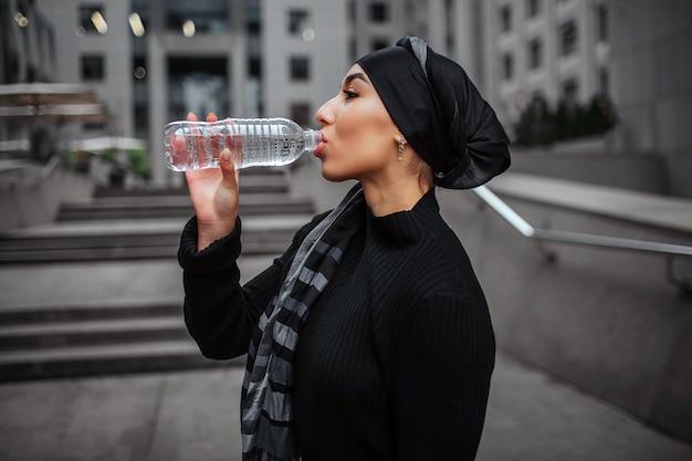 Młoda kobieta arabska wody pitnej z plastikowej butelki
