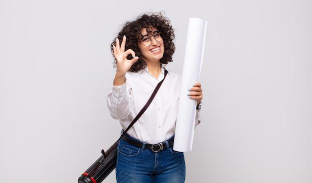 Młoda kobieta architekt czuje się szczęśliwa, zrelaksowana i usatysfakcjonowana, pokazując aprobatę w porządku gestem, uśmiechając się