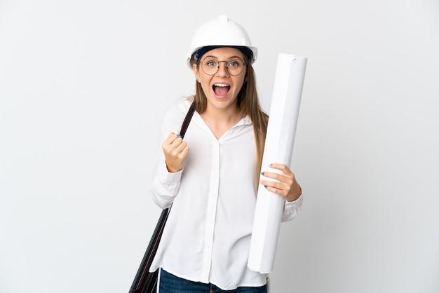 Młoda kobieta architekt litewski w kasku i trzymając plany na białym tle na białej ścianie świętuje zwycięstwo w pozycji zwycięzcy