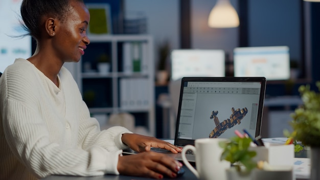 Młoda kobieta architekt pracujący w nowoczesnym programie cad w godzinach nadliczbowych siedząc przy biurku w biurze start-up