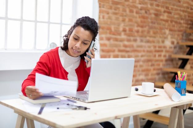 Młoda kobieta architekt rozmawia przez telefon, patrząc na plany domu. miejsce na tekst. koncepcja biura domowego.