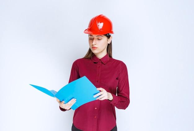 Młoda kobieta architekt w czerwonym kasku, czytanie ważnych notatek na białym tle.