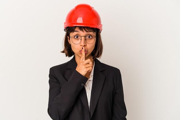 Młoda kobieta architekt z czerwonym kasku na białym tle dochowując tajemnicy lub prosząc o ciszę.