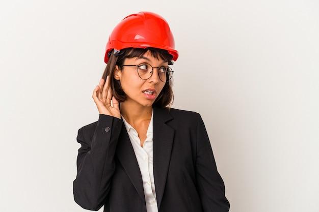 Młoda kobieta architekt z czerwonym kasku na białym tle próbuje słuchać plotek.