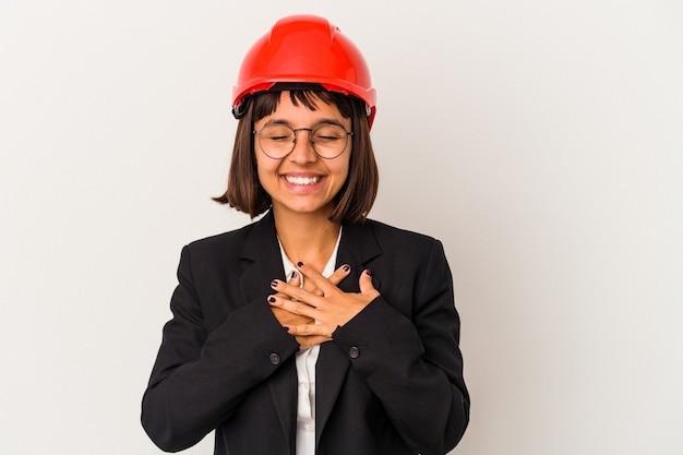 Młoda kobieta architekt z czerwonym kasku na białym tle śmiejąc się trzymając ręce na sercu, pojęcie szczęścia.