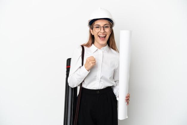 Młoda kobieta architekt z kaskiem i trzymając plany na białym świętuje zwycięstwo w pozycji zwycięzcy