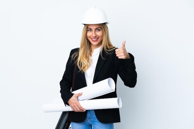 Młoda kobieta architekt z kaskiem i trzymając plany na izolowanych białej ścianie, dając kciuki do góry gest