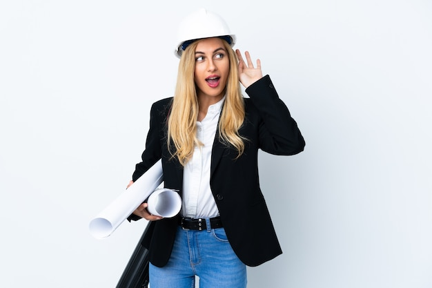 Młoda kobieta architekt z kaskiem i trzymając plany na pojedyncze białe słuchanie czegoś
