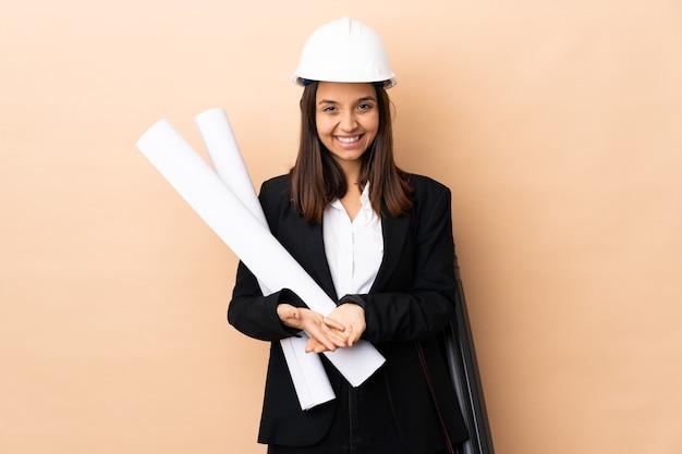 Młoda kobieta architekta posiadających plany na pojedyncze ściany gospodarstwa copyspace wyimaginowanej na dłoni, aby wstawić reklamę