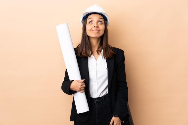 Młoda kobieta architekta posiadających plany na pojedyncze ściany i patrząc w górę