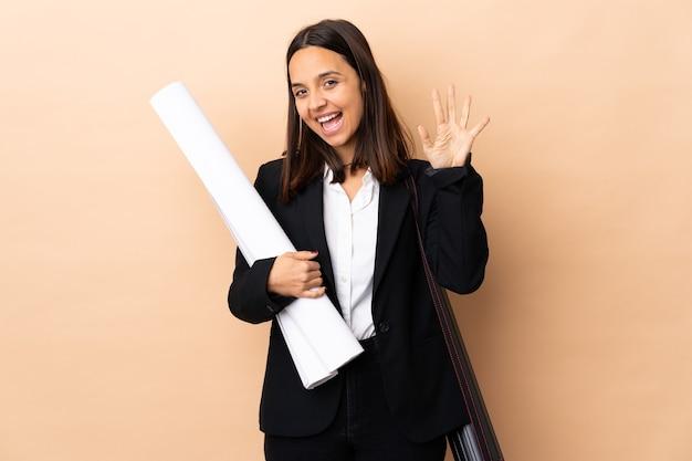 Młoda kobieta architekta posiadających plany na pojedyncze ściany licząc pięć palcami