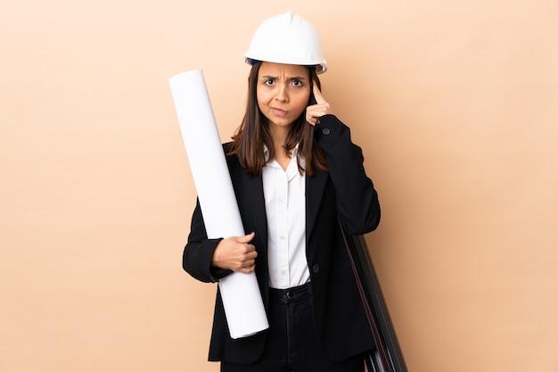 Młoda kobieta architekta posiadających plany na pojedyncze ściany myśli pomysł