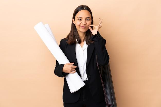 Młoda kobieta architekta posiadających plany na pojedyncze ściany przedstawiające znak gestu ciszy
