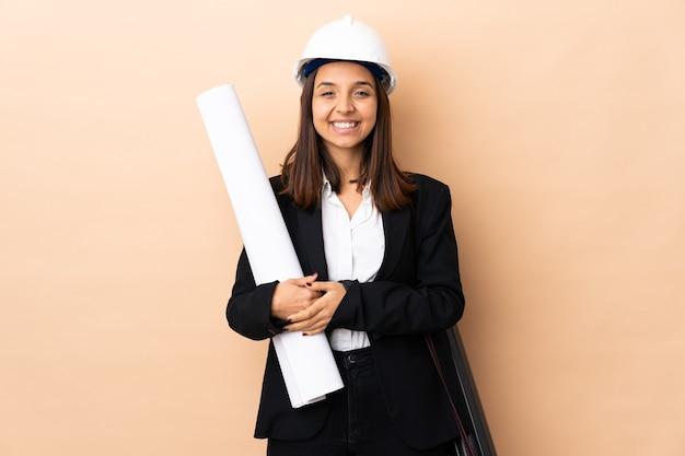 Młoda kobieta architekta posiadających plany na pojedyncze ściany śmiejąc się